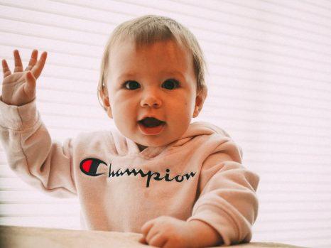 Bébé avec sweat à capuche Champion lève le bras droit